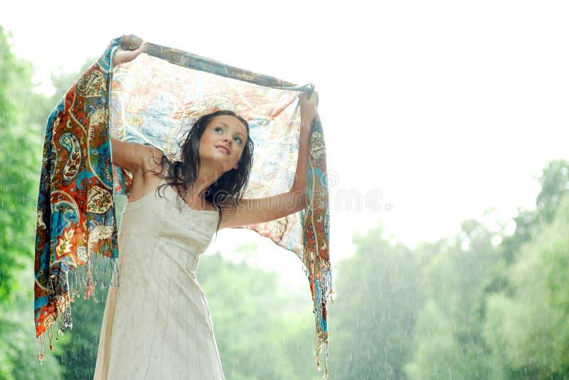Mädchenstütze unter Regentropfen stockfotografie