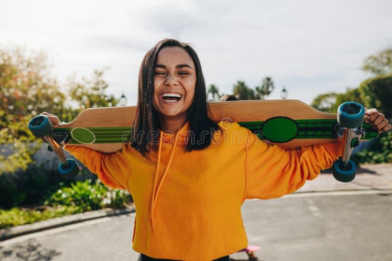Mädchenstellung in der Straße mit einem longboard stockfoto