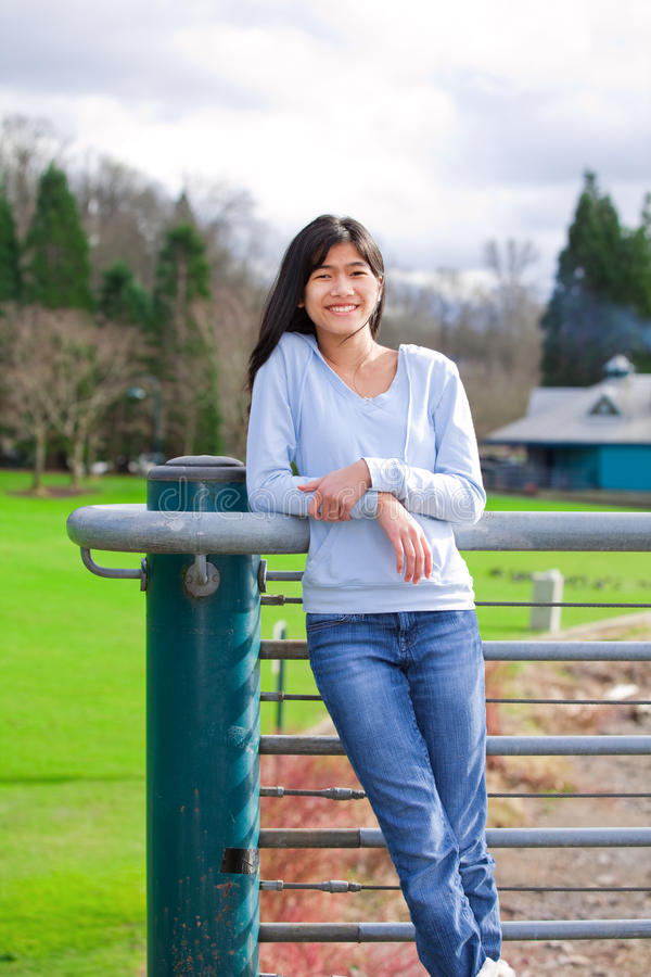 Mädchenstellung des jungen jugendlich, lehnend am Geländer am Park stockfotos