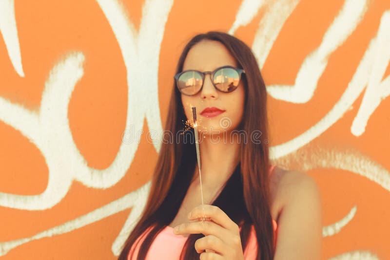 Mädchenstellung, die mit einer Wunderkerze aufwirft lizenzfreie stockbilder