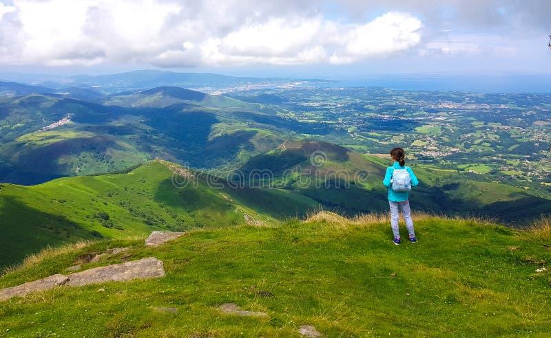 Mädchenstellung mit ihrer Rückseite, zum der Landschaft vom Berg Larrun zu sehen Abgrenzung zwischen der Grenze von Spanien und F stockfotografie