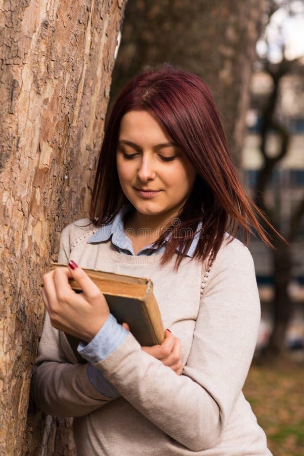 Mädchenstellung und -lesung ein Buch lizenzfreie stockfotos