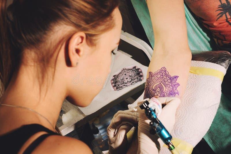 Mädchentätowierungskünstler macht Tätowierung auf einer Hand gegen blaue Gleichheit einer zukünftigen Tätowierung unter Verwendun lizenzfreie stockfotografie
