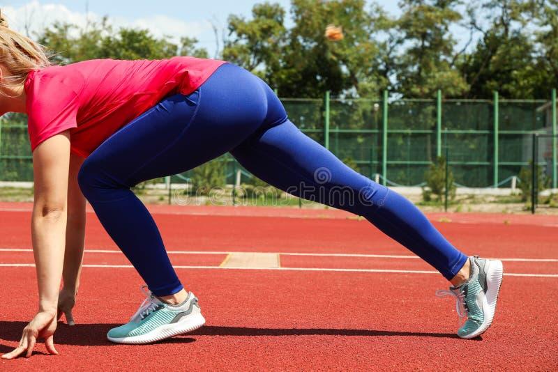 Mädchentief, das beginnt, auf roter athletischer Bahn zu laufen lizenzfreie stockfotos