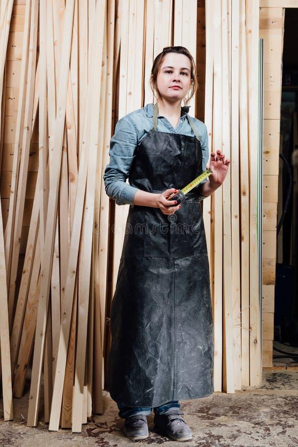 Mädchentischler mit einem Maßband auf einem Hintergrund von hölzernen Stücken in der Werkstatt stockbild
