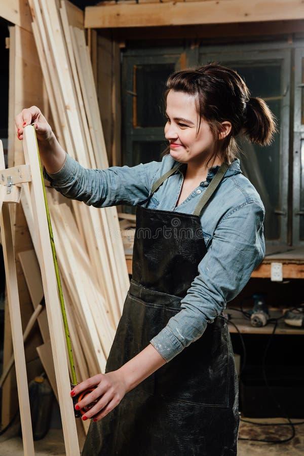 Mädchentischler mit einem Maßband auf einem Hintergrund von hölzernen Stücken in der Werkstatt stockfotos