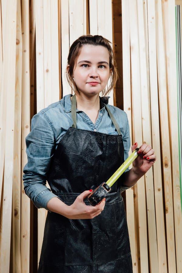 Mädchentischler mit einem Maßband auf einem Hintergrund von hölzernen Stücken in der Werkstatt stockbilder