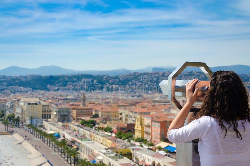 Mädchentourist auf münzenbetriebenbinokularem von hinten, genießend, Panoramablick von Nizza, Frankreich betrachtend lizenzfreie stockbilder
