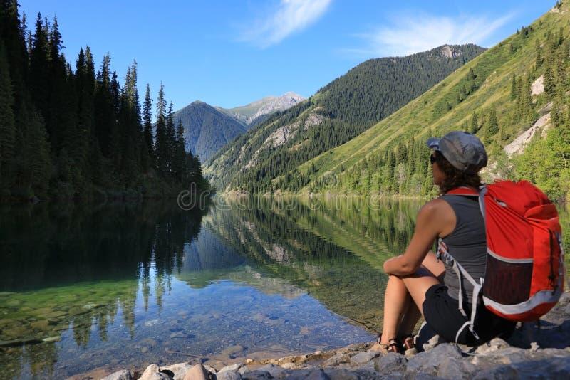 Mädchentourist, der auf dem Ufer von See Kolsay, Kasachstan sitzt lizenzfreies stockbild