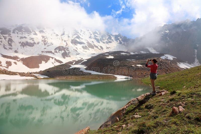 Mädchentourist macht Fotos auf Handyansichten des Gebirgssees stockfotos