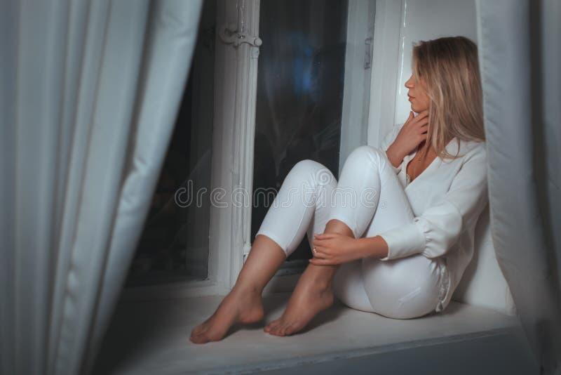 Mädchenträume des Sitzens am Fenster stockfotos