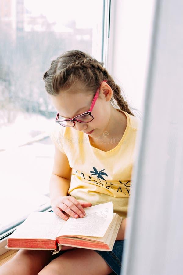 Mädchentween mit Glas- und Zopflesebuch am Fensterbrett in ihrem Raum stockbilder