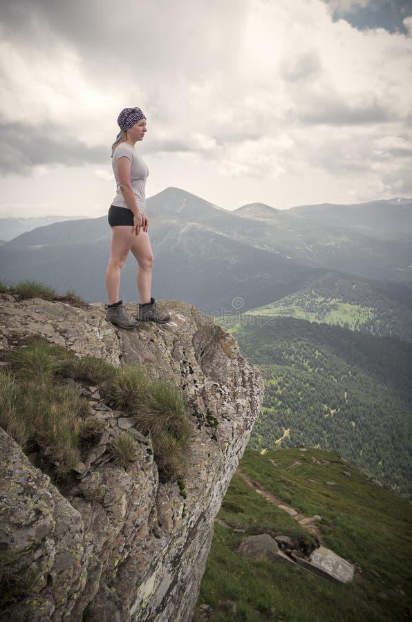Mädchenwanderer, der auf Klippe steht und die Berge betrachtet stockbilder