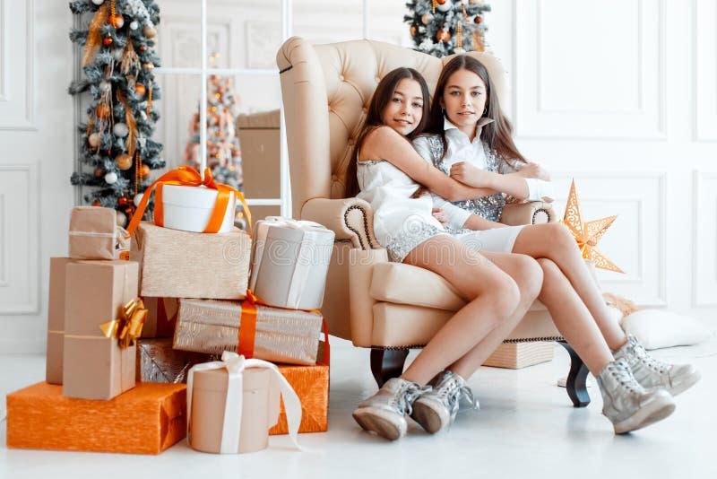 Mädchenzwillinge vor dem Tannenbaum Neues Jahr ` s Eve Weihnachten Gemütlicher Feiertag am Tannenbaum mit Lichtern lizenzfreie stockfotografie