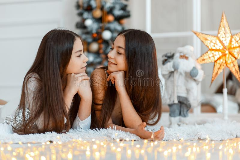 Mädchenzwillinge vor dem Tannenbaum Neues Jahr ` s Eve Weihnachten Gemütlicher Feiertag am Tannenbaum mit Lichtern lizenzfreies stockfoto