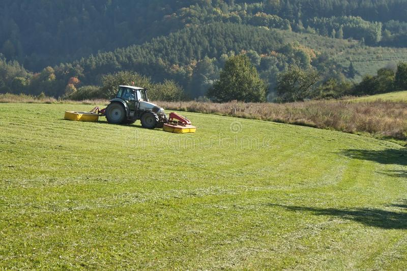 Mähende Bergwiese des Traktors lizenzfreie stockfotos