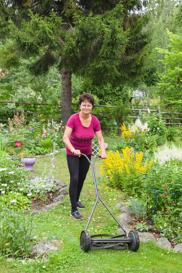 Mähendes Gras der positiven älteren Frau mit Rasenmäher im Garten lizenzfreie stockfotos