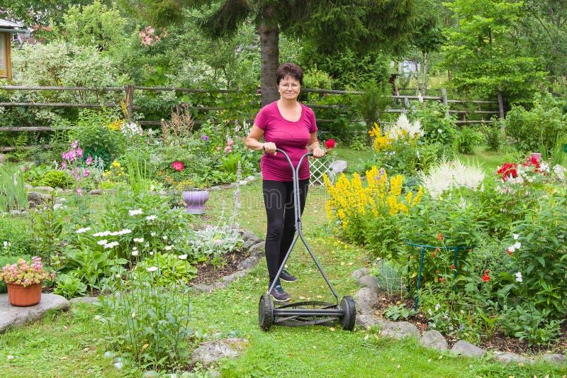 Mähendes Gras der positiven älteren Frau mit Rasenmäher im Garten stockfoto