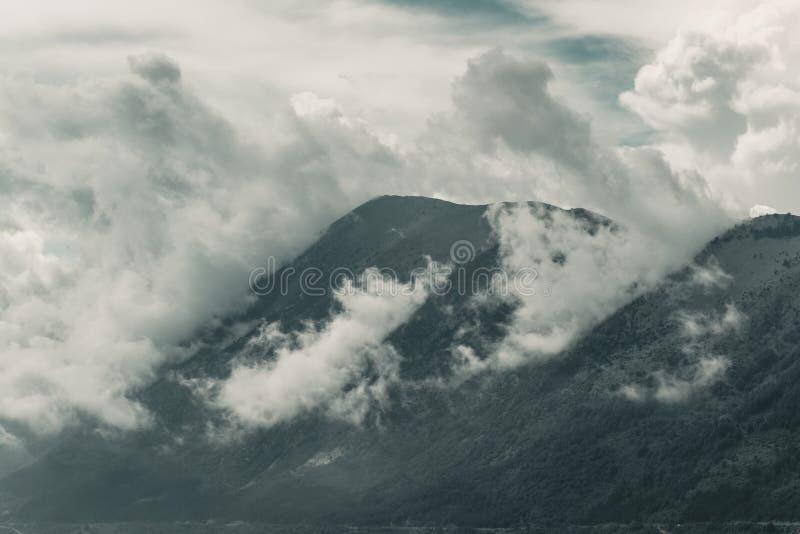 Mäktig bergskedja som täckas av moln royaltyfria foton
