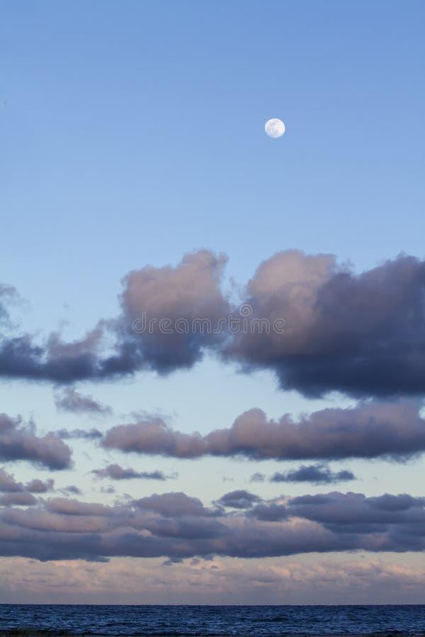 Mäktig himmel på solnedgången med en fullmåne över och lager av moln som färgas med rosa färger som lutning ner till horis fotografering för bildbyråer