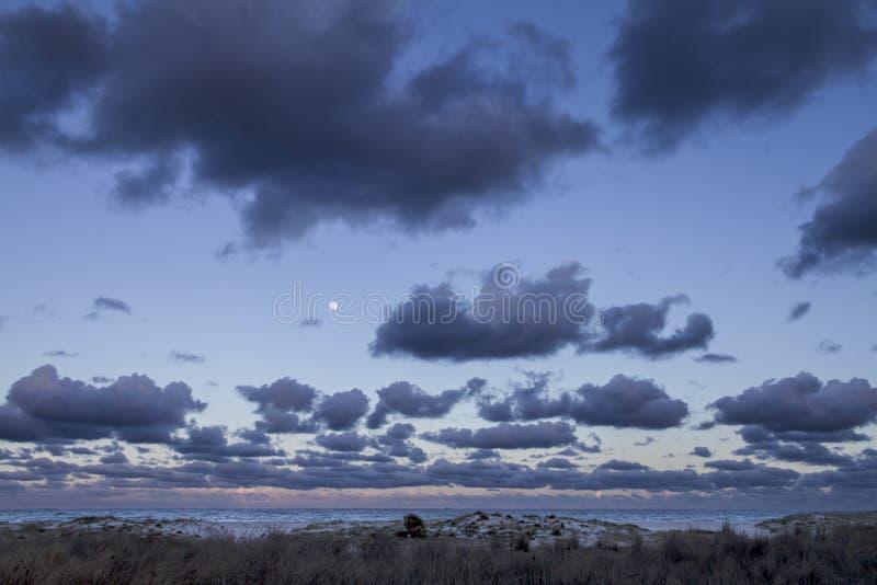 Mäktig solnedgånghimmel med fullmånen och lagren av moln som sluttar ner in mot horisonten över det mörka havet och det vitt arkivfoton