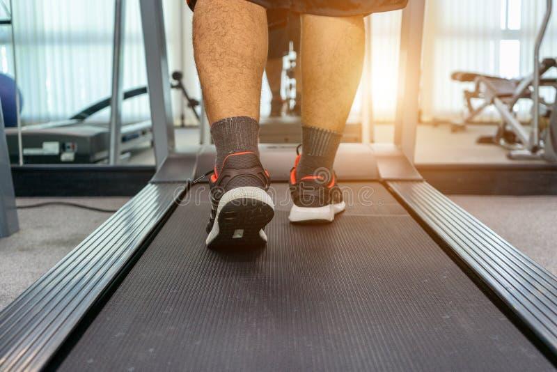 Män övar, genom att köra på en trampkvarn, når de har arbetat i en inomhus konditionmitt för aktivitet som en sund kropp Begrepps arkivbilder