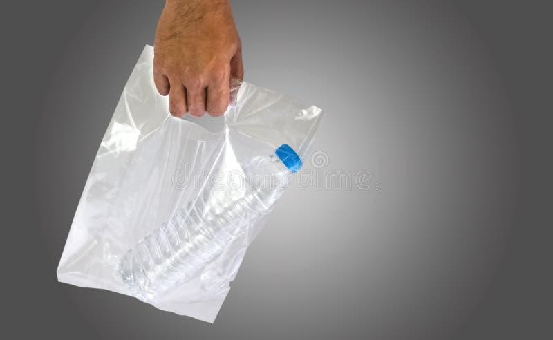 Män bar plastpåsar, vattenflaskor Båda förorenar royaltyfri bild