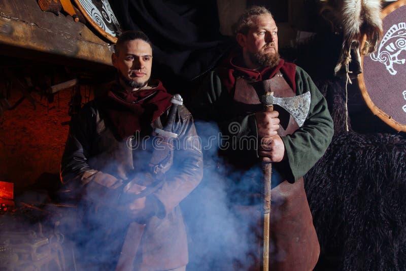 Män för härd två för brand för hud för sköld för yxa för dräkt för vapen för krigare för smed för smedja för reenactment för kugg arkivbild