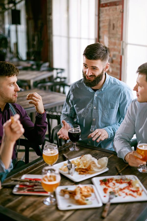 Män i bar som dricker öl och äter mat fotografering för bildbyråer