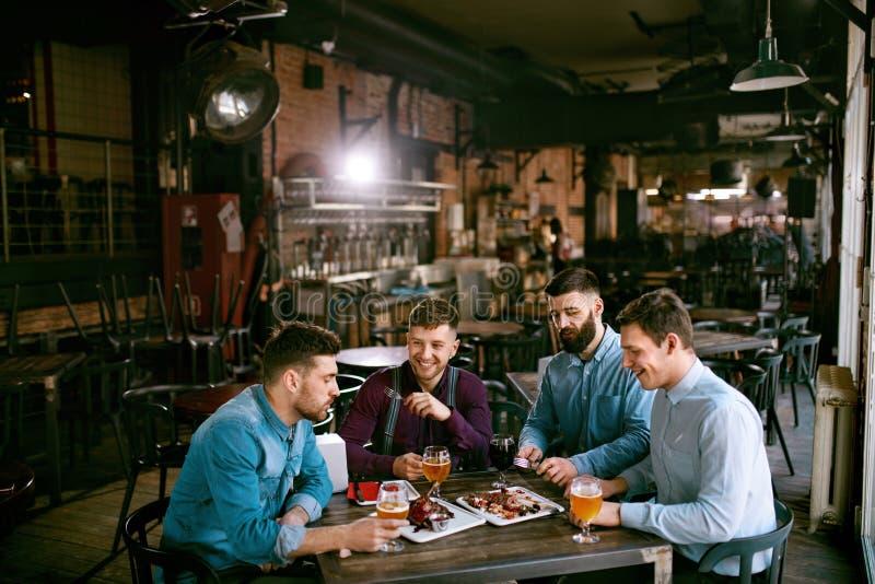 Män i bar som dricker öl och äter mat arkivfoto