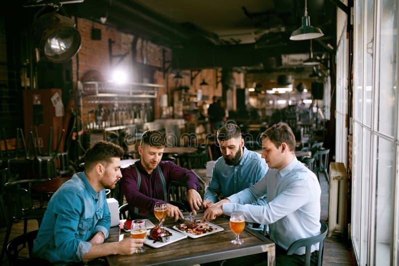 Män i bar som dricker öl och äter mat royaltyfri foto