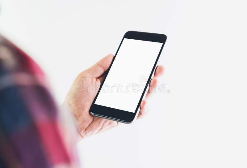 Män i den röda skjortan som bär en tom skärm för svart telefon som är passande för diagram som används för annonsering royaltyfri foto
