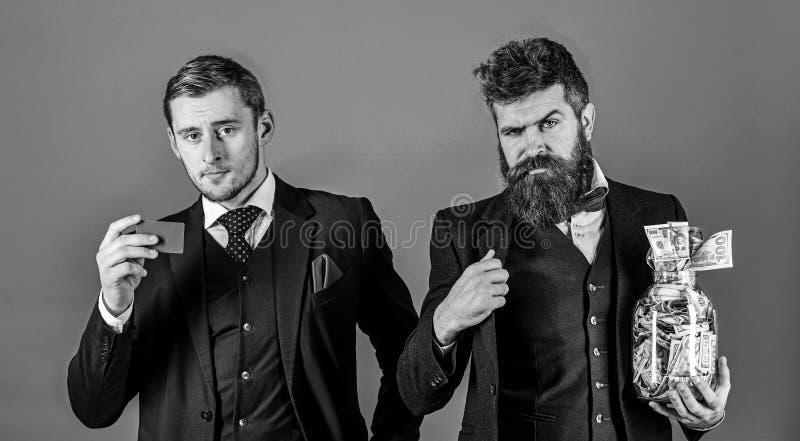 Män i dräkt, affärsmän med kruset som är full av kassa och kreditkort, blå bakgrund Finanskonsulentbegrepp bankcarden fotografering för bildbyråer