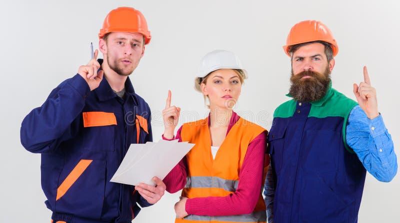 Män i hårda hattar, likformig och kvinna Lösning av problembegrepp royaltyfri bild