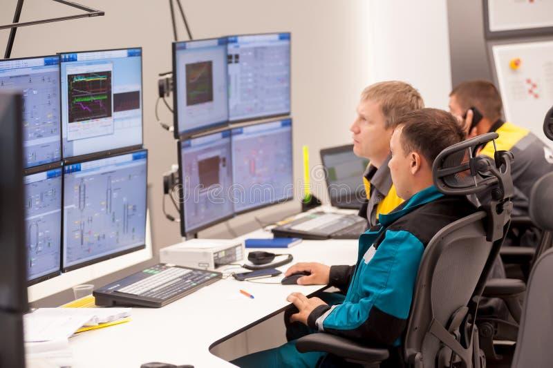 Män i kontrollrummet på fabriken av polypropen arkivfoton