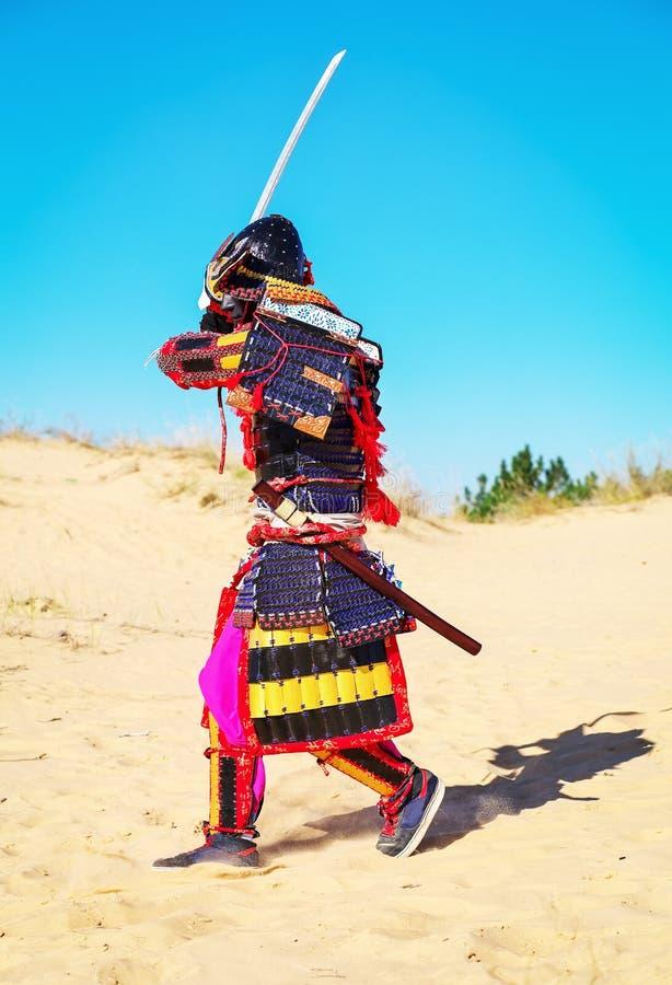 Män i samurajpansar med svärdspring arkivbilder