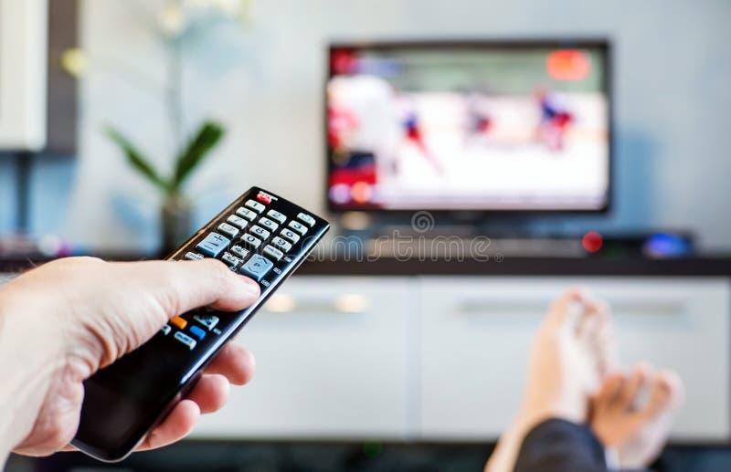 Män med fjärrkontrollen, framdel av televisionen royaltyfri fotografi