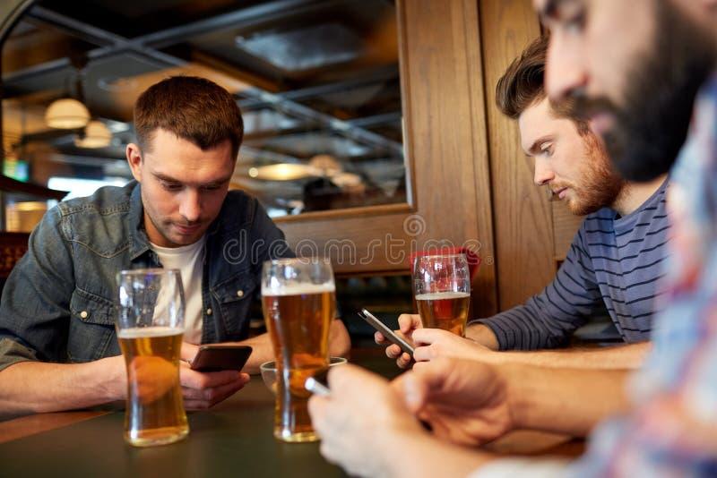 Män med smartphones som dricker öl på stången eller baren arkivbilder