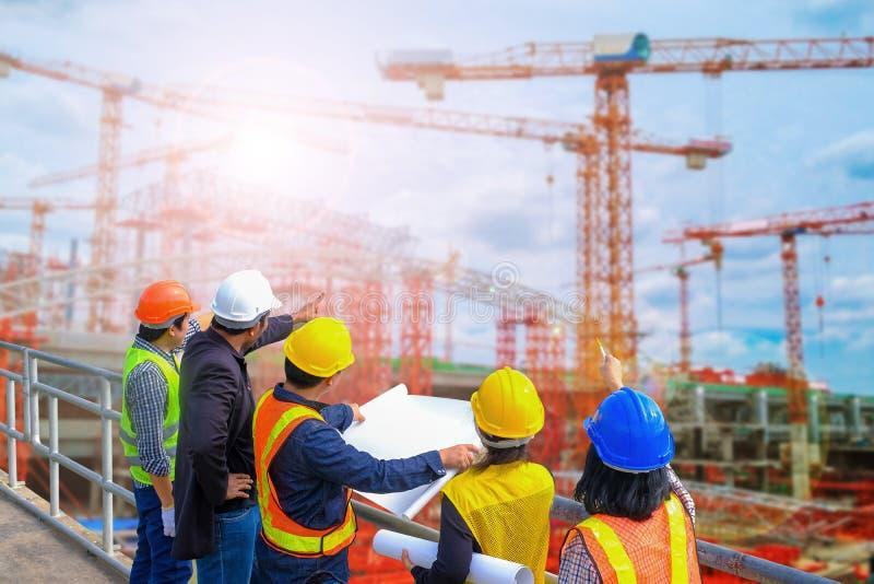 Män och kvinnamötet med teknikerer och arbetsledare står läsa ritningarna konstruktionsplatsen royaltyfri bild