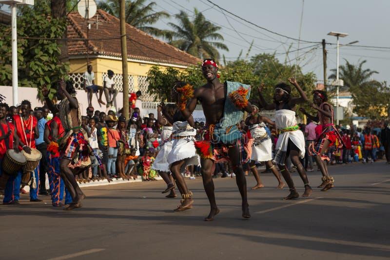 Män och kvinnor som bär traditionella kläder på, ståtar under karnevalberömmarna i staden av Bisssau royaltyfri foto