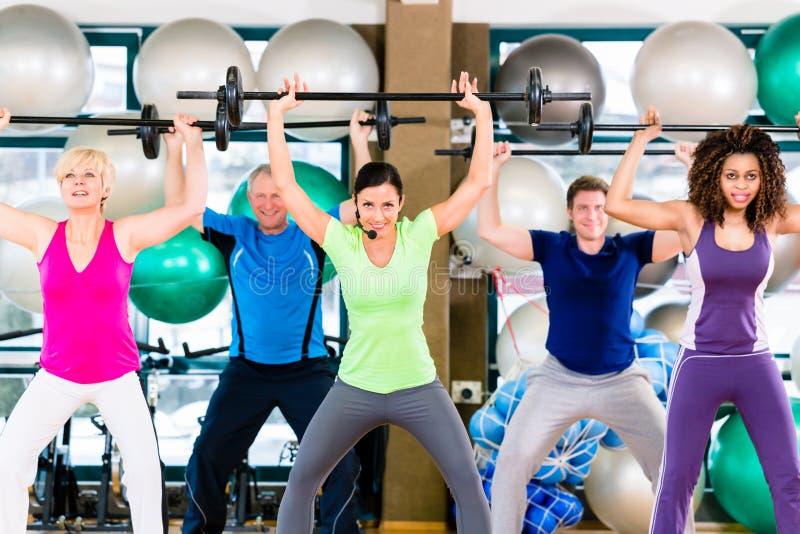 Män och kvinnor som lyfter skivstången i idrottshall arkivfoto