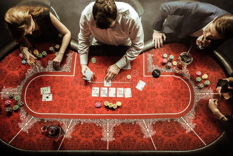 Män och kvinnor som spelar poker i kasino arkivfoton