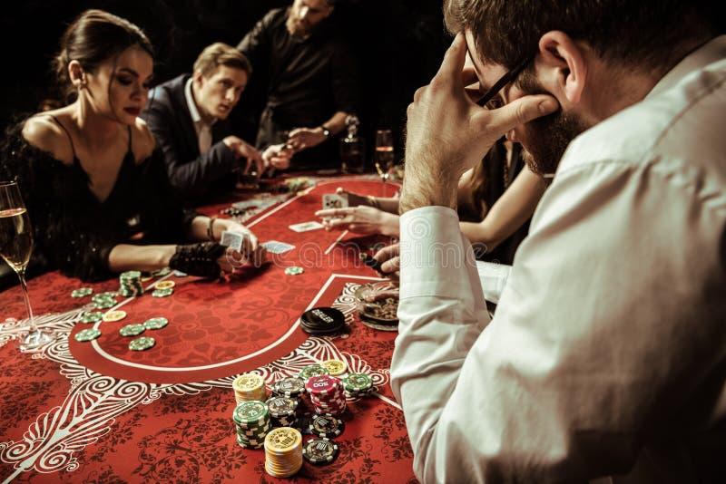 Män och kvinnor som spelar poker i kasino arkivfoto