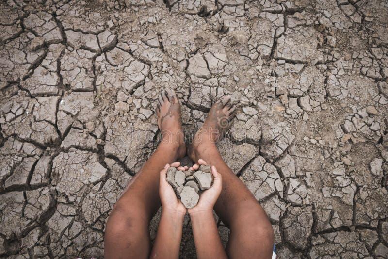 Män på knäckt jordning torkar tack vare torkan royaltyfri foto