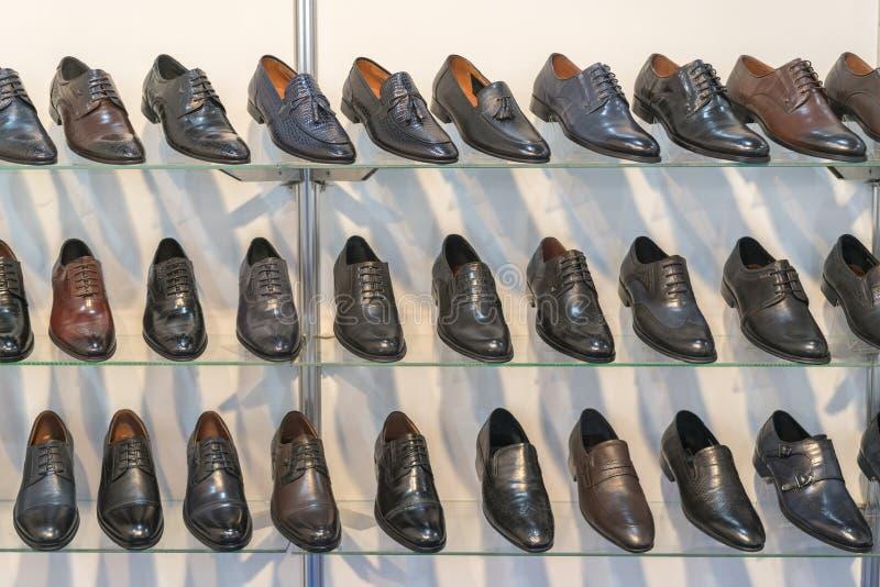 Män piskar skor på hyllan i lagret Kuggar i lagret av kläder och tillbehör Hyllor med stilfulla mäns skor royaltyfri fotografi