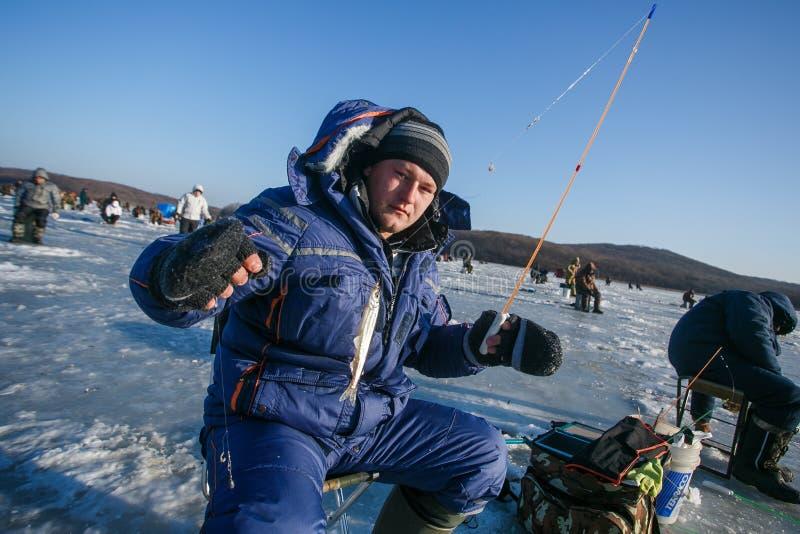 Män sitter på isen och fisken Vinterfiske i Ryssland royaltyfria bilder
