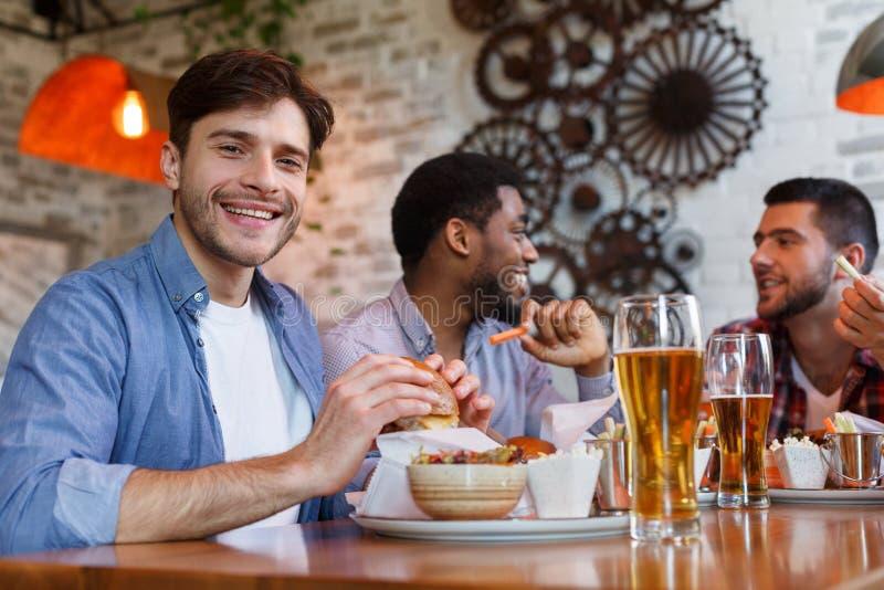 Män som äter hamburgare och dricker öl i bar royaltyfri foto