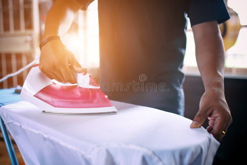 Män som arbetar strykning, är mannen som är starkare för frun royaltyfria bilder
