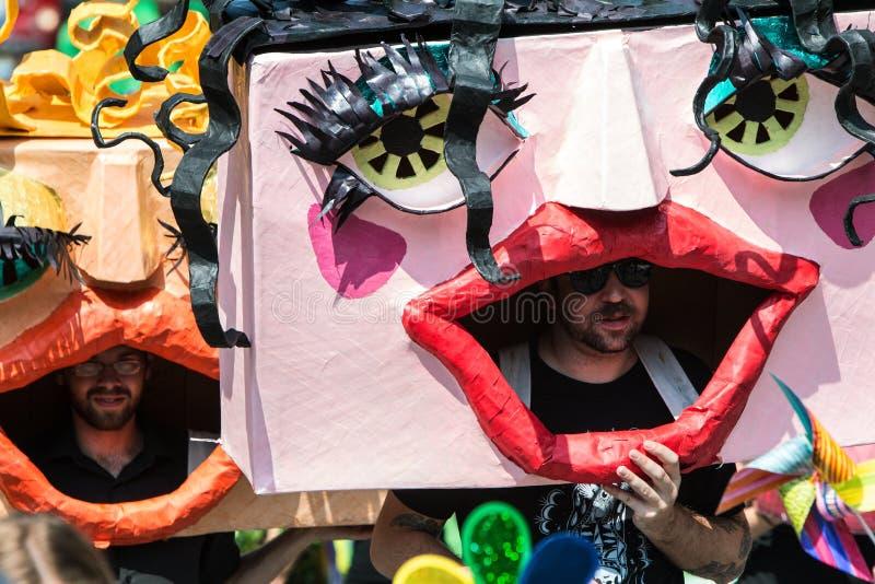 Män som bär enorma handgjorda maskeringar, går i den Atlanta festivalen ståtar royaltyfri foto