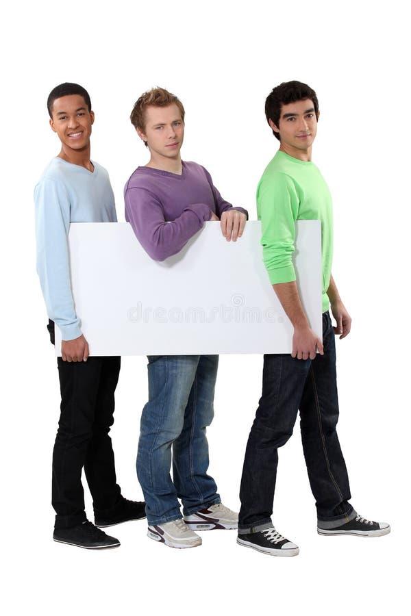 Män som bär ett tomt bräde royaltyfria foton